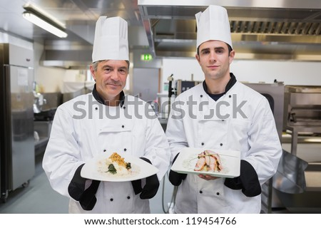 Male Chef's presenting their dishes in the kitchen - stock photo