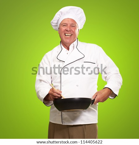 Male Chef Stirring A Non Stick Pan On A Green Background - stock photo