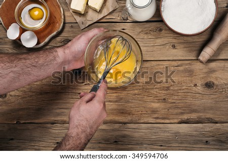 Male chef whipping eggs in the bakery on wooden table. Ingredients for cooking flour products or dough  (flour, eggs, milk, butter). Top view with copy space - stock photo