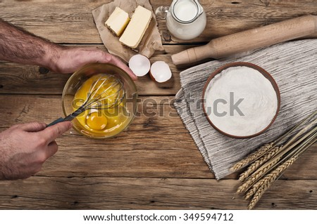 Male chef whipping eggs in the bakery on wooden table. Top view with copy space.  Ingredients for cooking flour products or dough  (flour, eggs, milk, butter) - stock photo