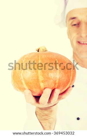 Male chef with a pumpkin - stock photo