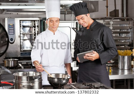 Male chef with digital computer assisting colleague in preparing food at kitchen