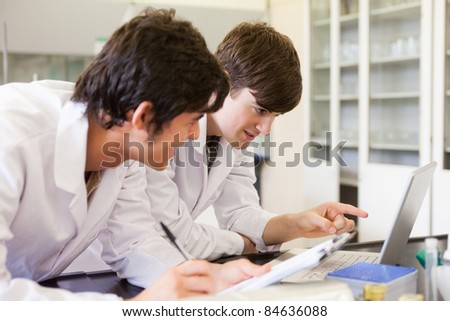 Male chemistry students writing a report in a laboratory - stock photo