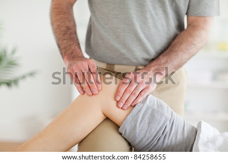Male Chiropractor massaging a charming woman's knee in a room - stock photo