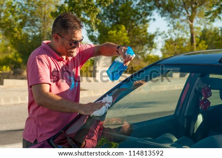 Male cleaning his car windscreen outdoors - stock photo