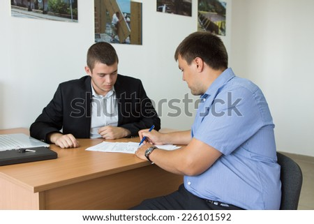 Male Client Signing Written Document on Wooden Desk of Young Real Estate Agent Inside the Firm. - stock photo
