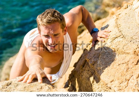 Male climber climbing on the rocks against sea water. Rockclimbing guy in swimwear reaching for a next stone grip on a steep mountain. Summer activity extreme sports outdoors. Focus on the face - stock photo