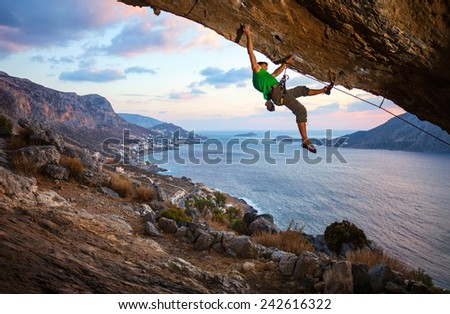 Male climber climbing overhanging rock against beautiful view of coast below - stock photo