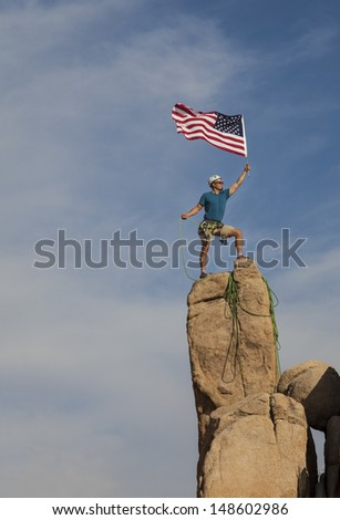 Male climber conquers the summit of a challenging rock spire.