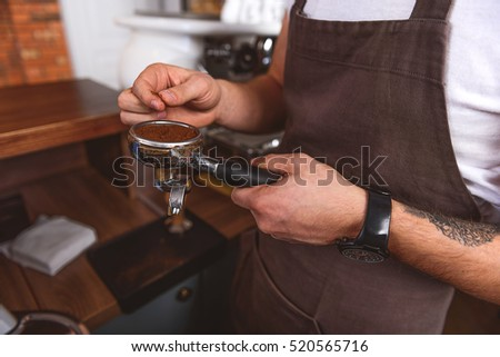 male coffeemaker standing with portafilter
