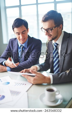 Male colleagues discussing electronic data in touchpad - stock photo