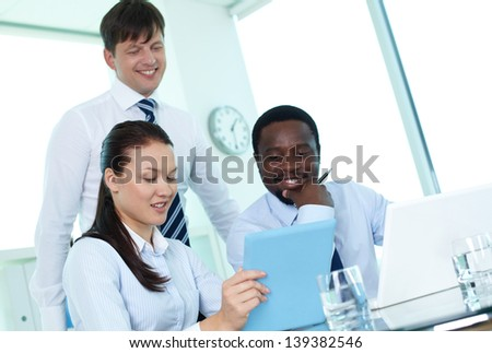 Male colleagues listening to young employee making electronic presentation at meeting - stock photo