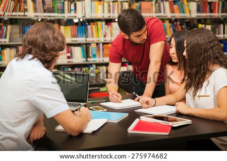 Male college student explaining some school work to his colleagues while studying in the library - stock photo