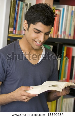Male college student reading in a library - stock photo