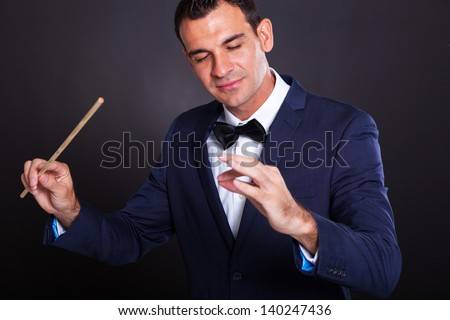 male conductor on black background - stock photo