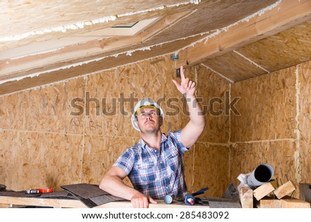 Male Construction Worker Builder Pointing and Looking Up at Ceiling, Admiring Handiwork, Inside Unfinished Home with Exposed Particle Plywood Board - stock photo
