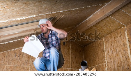 Male Construction Worker Builder Wearing White Hard Hat Crouching on Elevated Scaffolding near Ceiling Sky Light and Reading Plans in Unfinished Home with Exposed Plywood Particle Board - stock photo