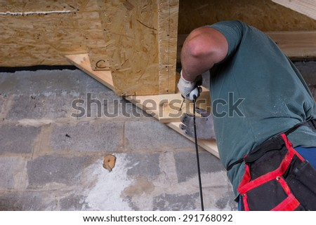 Male Construction Worker Builder with Drill Building Frame for Stairs in Basement of Unfinished Home with Exposed Cement Wall - stock photo