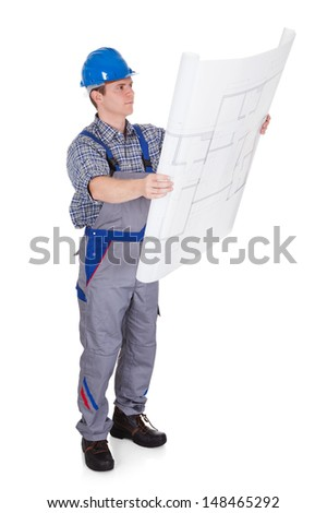 Male construction worker looking at blue prints isolated on white background - stock photo