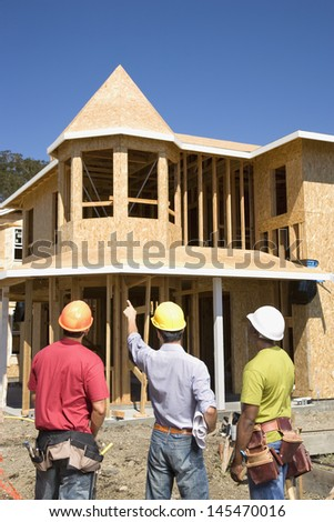 Male construction workers pointing at house under construction - stock photo