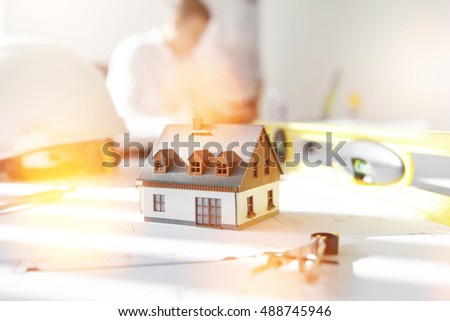 Male contractor developing construction plan, sitting in office with scale model residential building or house in foreground. Young interior designer working on new real estate project. Flare sun