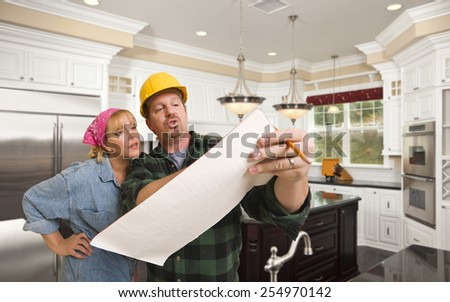 Male Contractor in Hard Hat Discussing Plans with Woman in Custom Kitchen Interior. - stock photo