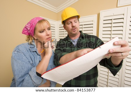 Male Contractor in Hard Hat Discussing Plans with Woman in Room. - stock photo