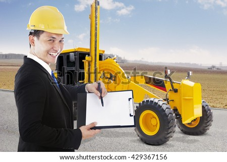 Male contractor showing empty clipboard with road grader on the street, shot outdoors