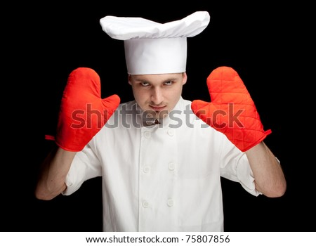 male cook in white uniform and hat with red kitchen gloves, black background - stock photo