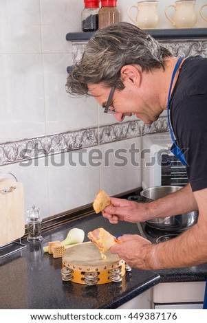Male cooking, using chicken drumsticks in  a somewhat different way