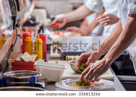male cooks preparing meals in restaurant kitchen - stock photo