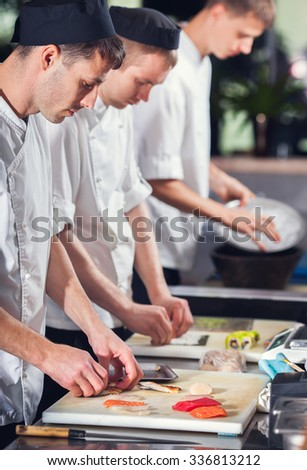 male cooks preparing sushi in the restaurant kitchen - stock photo