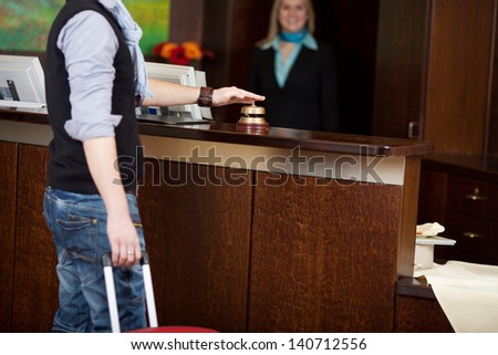 male costumer with baggage ringing bell at hotel counter - stock photo
