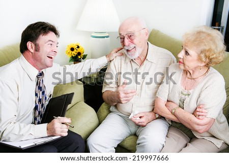 Male counselor taking sides with the husband against the wife.   - stock photo