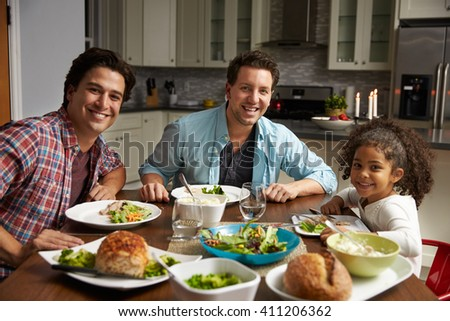 Male couple and black daughter dining at home look to camera - stock photo