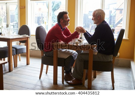Male couple holding hands at a restaurant table, full length - stock photo