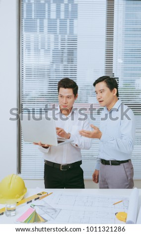 Male coworkers discussing ideas  about project in office, architectural concept