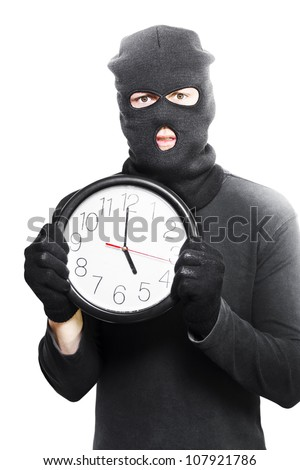 Male criminal in a black mask holding a stolen clock showing five oclock in a knock off time conceptual isolated on white background - stock photo