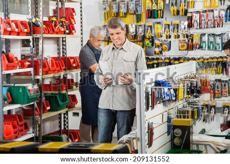 Male customer choosing soldering iron with worker working in background at hardware store - stock photo