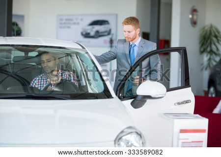 male customer in car showroom with car seller, young man sitting in car and  trying on the comfort of the car - stock photo
