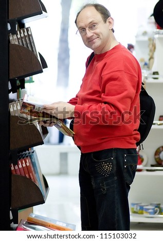 Male customer reading in a book store - stock photo