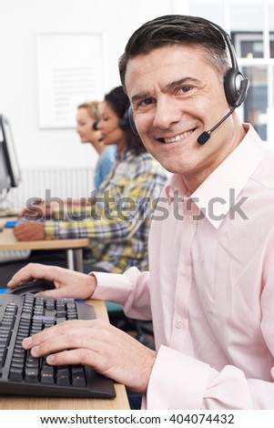 Male Customer Services Agent In Call Center - stock photo
