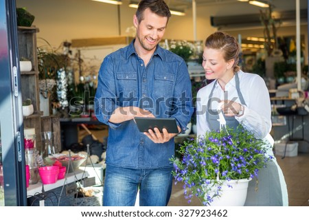 Male customer using digital tablet while standing by florist holding potted plant in shop - stock photo