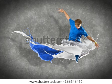 male dancer jumped surrounded by splashes of paint