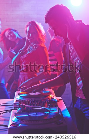 Male deejay adjusting sound on background of group of energetic dancers - stock photo