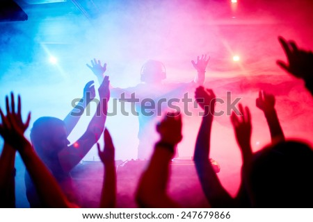 Male deejay in front of dancing crowd - stock photo