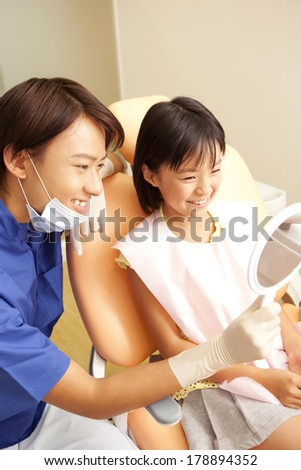 male dentist and a Japanese woman in the mirror after treatment
