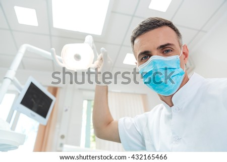 Male dentist doing procedure and looking at camera in dental office - stock photo