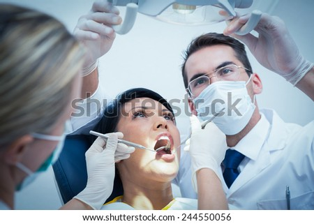 Male dentist with assistant examining womans teeth in the dentists chair - stock photo