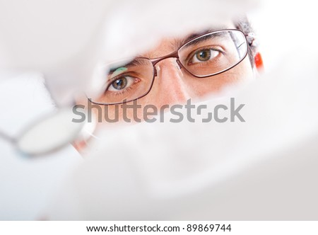 Male dentist working on teeth with an instrument - stock photo